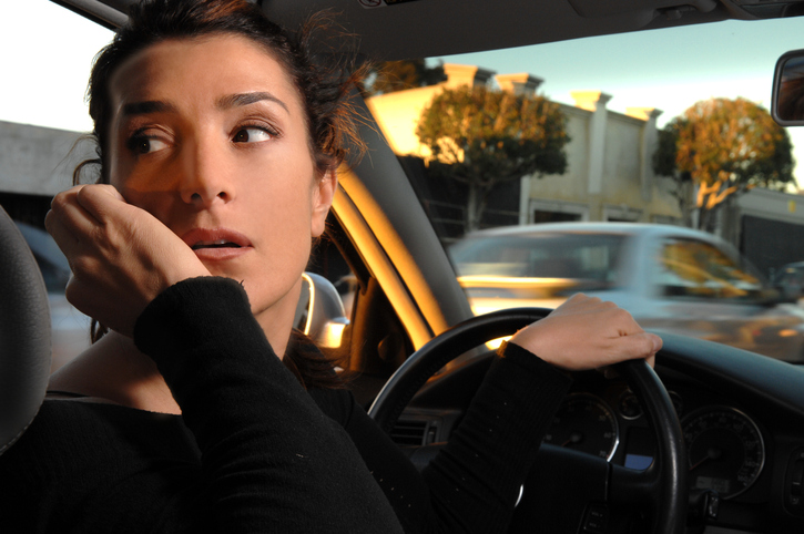 Young woman driving without her eyes on the road